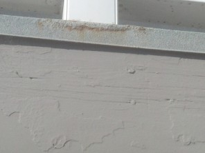 Rust bleeding through coating indicates moisture intrusion.