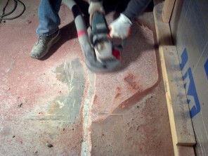 Grinding the old floor for new to adhere to.