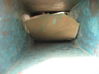 A scupper with a failing coating peeling away from the copper.